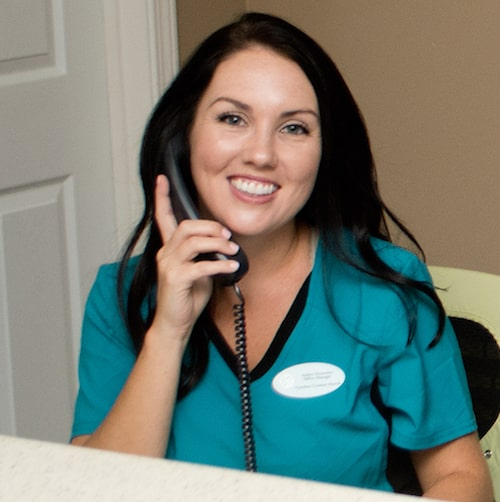 One of our front desk team on the phone and smiling