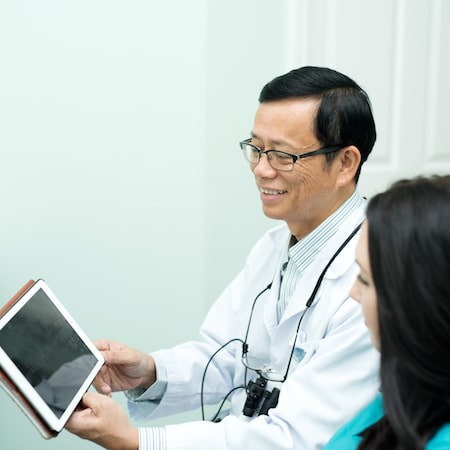 Dr. Tan Binh Nguyen looking at his tablet with his dental assistant
