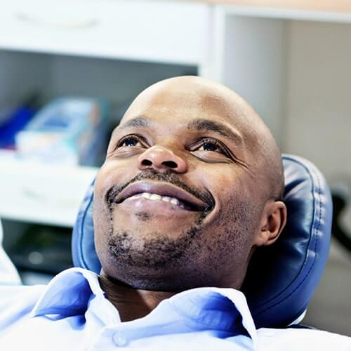 Happy male patient on dentist chair