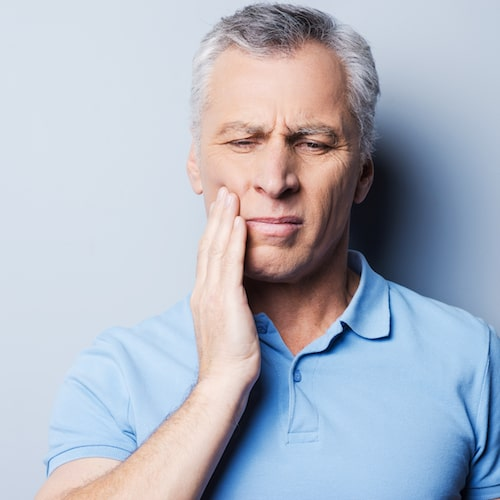 Older man with a toothache holding his face in pain