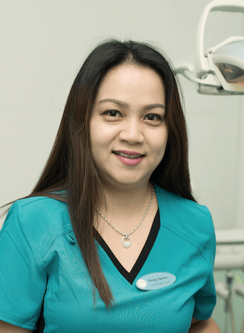 Our dental assistant Nung smiling in a treatment room