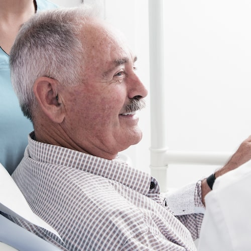 Side view of an older man with grey hair smiling in a dental chair