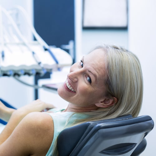 Older lady with grey hair in a dentist chair turning back and smiling