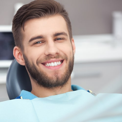 Young man with a beard, short brown hair, and a big smile sitting in a treatment chair