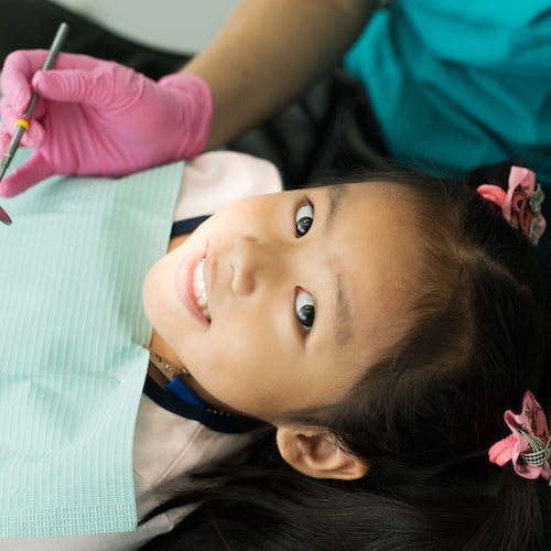 Young girl sitting in the dentist chair and looking up while smiling