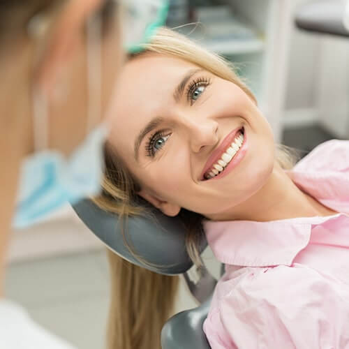 A blonde female patient smiling on dentist chair