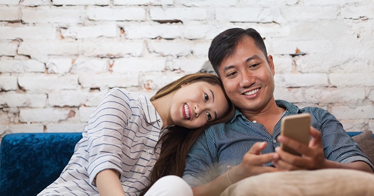 A middle aged couple sitting on a sofa together after enjoying same-day dentistry with CEREC technology